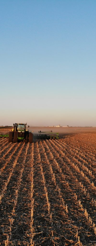 Tractor spraying liquid fertilizer on a field in the fall.