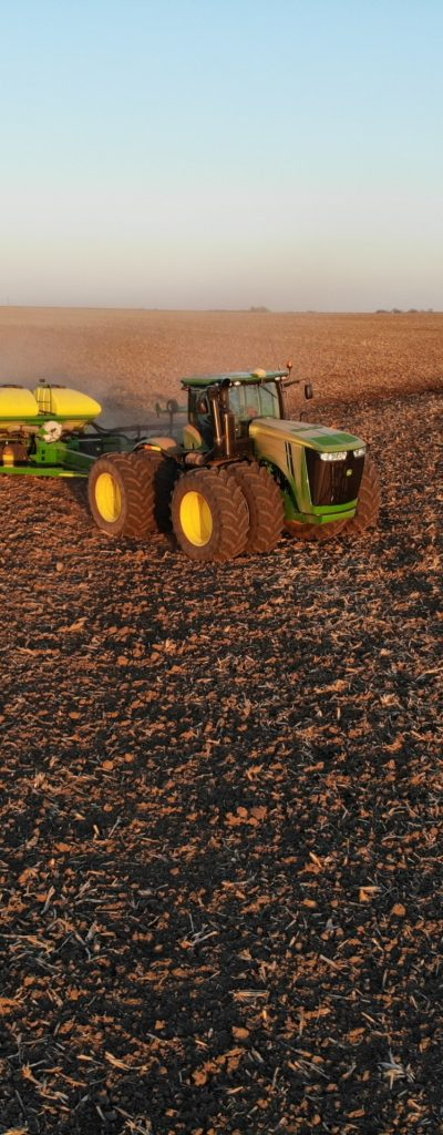 green tractor pulling a yellow fertilizer tank in a field.