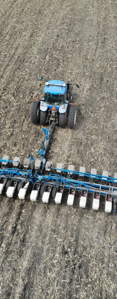 A blue tractor pulling a liquid fertilizer trailer.