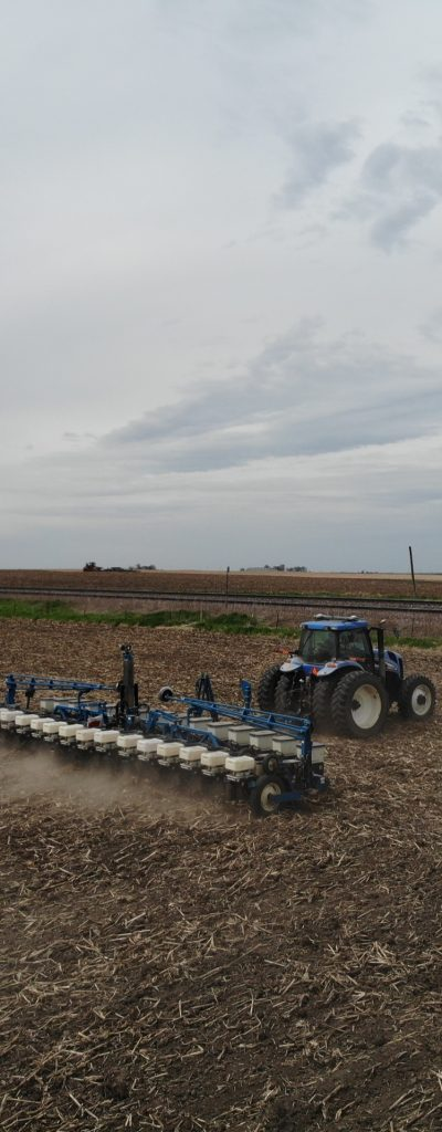 A blue tractor pulling a liquid fertilizer trailer on an empty field.