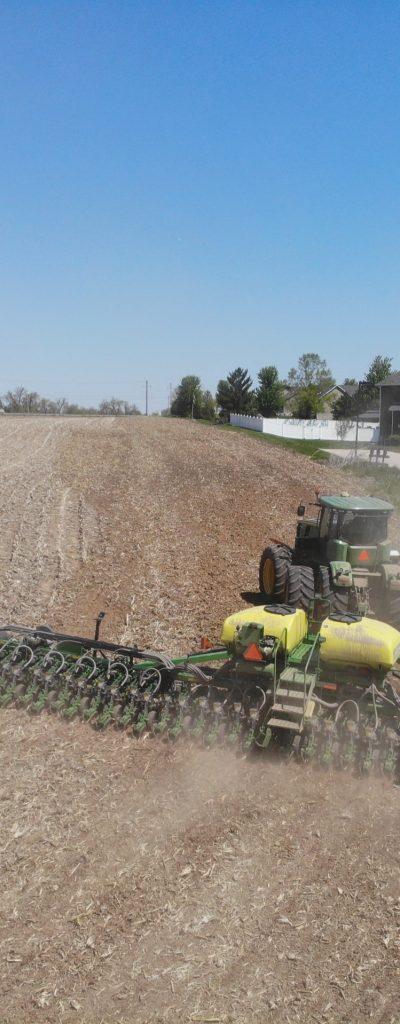 Green tractor pulling a sprayer though a farm field.