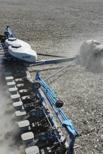 Green tractor pulling a blue spray trailer which is depositing liquid chemical fertilizer on harvested ground.