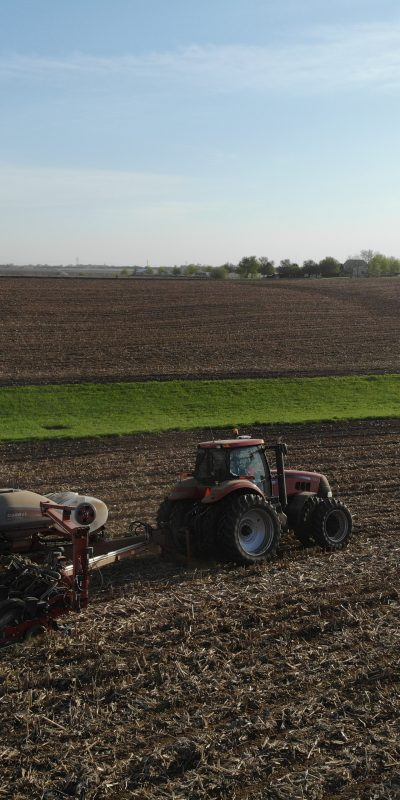 A red tractor pulling a fertilizer tank on a field.