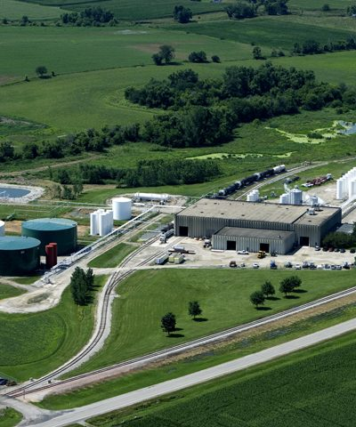 Aerial view of a chemical fertilizer warehouse with train tracks and roads leading to it.