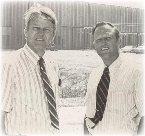 Black and white photo of two white men in white shirts and ties outside.