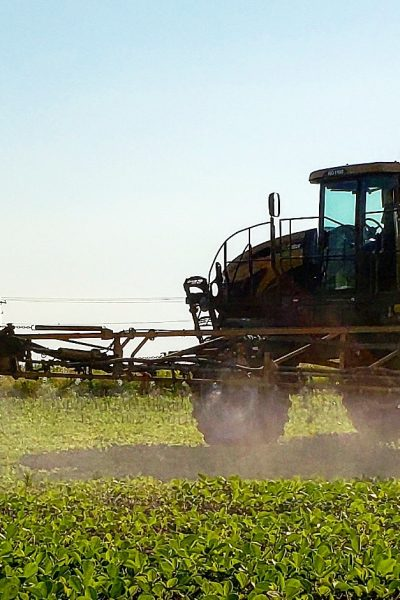 A tractor with sprayer arms distributing liquid fertilizer on a soybean field in the morning.